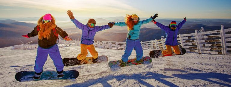 group of girls jumping on snowboards